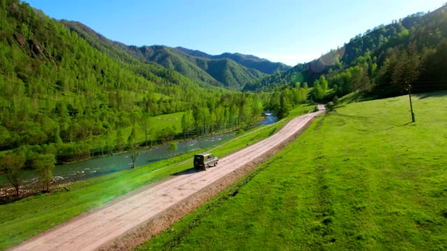 FHD FullHD aerial of vehicle driving towards the sunrice. Mid-air shot suv car driving video