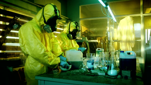 Fully Armed Special Anti-Narcotics Task Forces Soldier Arrests Two Clandestine Chemists Working in the Drug Producing Underground Laboratory. Chemists Raise Hands and Surrender. A lot of Functional Drug Production Equipment is Standing Around. video