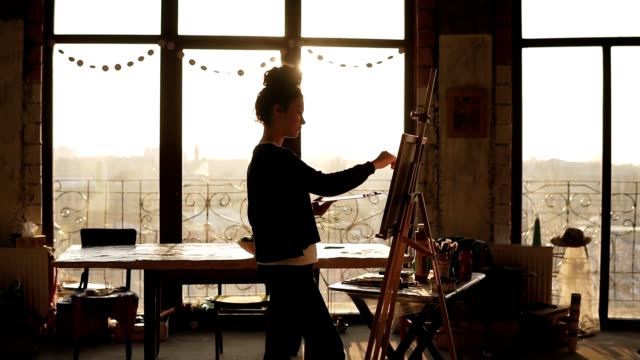 fully concentrated sophisticated female artist in her 20's is drawing picture on easel. the sun behind lits up the art studio and turns it into inspiring environment of creativity. - painter stock videos & royalty-free footage