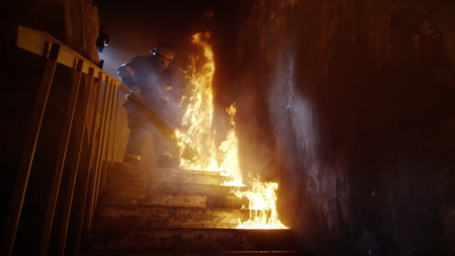 fully equipped firefighters coming down on burning stairs. building is on fire. shot in slow motion. - firefighter stock videos and b-roll footage
