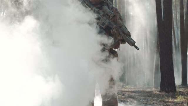 Fully Equipped Soldier comes out of the smoke in the Middle of the Forest video
