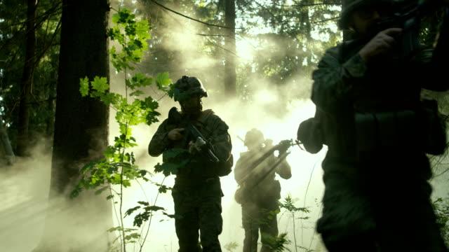 vídeos de stock, filmes e b-roll de totalmente equipados soldados vestindo uniforme de camuflagem, atacando o inimigo, rifles prontos para atirar. operação militar em ação, esquadrão executando em formação através da densa floresta de smokey. - conflito