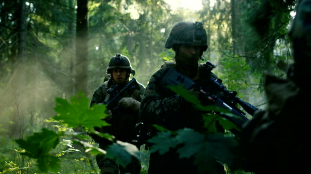 vídeos de stock e filmes b-roll de fully equipped soldiers wearing camouflage uniform attacking enemy, rifles ready to shoot. military operation in action, squad running in formation through dense smokey forest. slow motion footage. - fuzileiro naval
