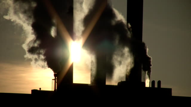 Fumes billow from giant chimney amidt the sunlight (High Definition) video