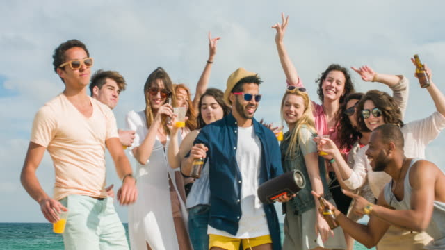 Fun dancing in the beach Group of friends having a party in the beach. bluetooth stock videos & royalty-free footage