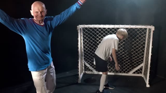 Fun Family Game. Grandfather Is Scoring Goal Into Gate Of Grandson And Celebrating It video
