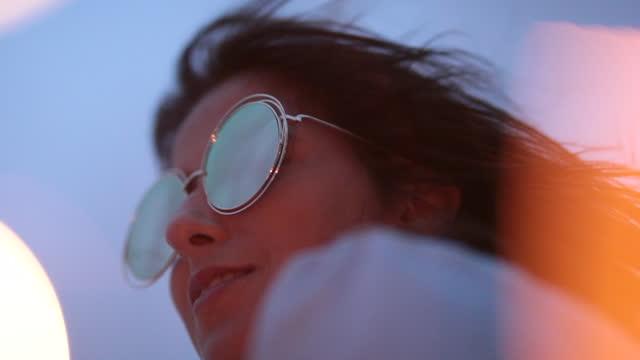 fun girl носить большие забавные круглые солнцезащитные очки снаружи с огнем sparkels на переднем плане - white background стоковые видео и кадры b-roll