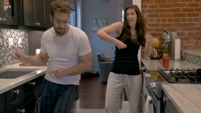 Fun loving man and woman dancing for the camera wearing pajamas