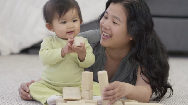 Fun with Toy Blocks An asian baby sits on the floor and plays with toy blocks with her mother. filipino ethnicity stock videos & royalty-free footage