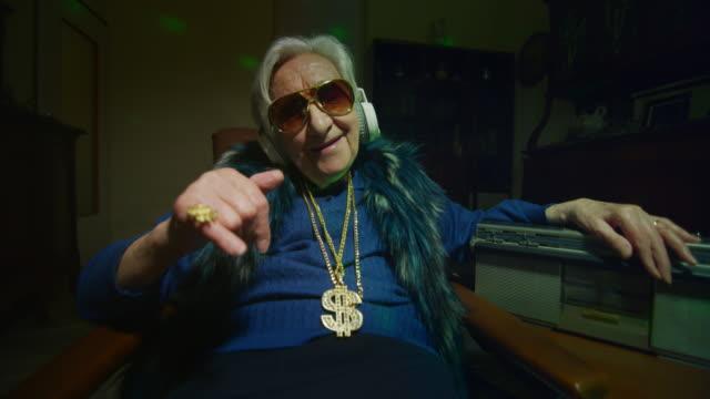 eine funky gekleidete, fröhliche, modern reiche seniorin mit sonnenbrille zeigt einen haufen geldscheine in der kamera. - bizarr stock-videos und b-roll-filmmaterial