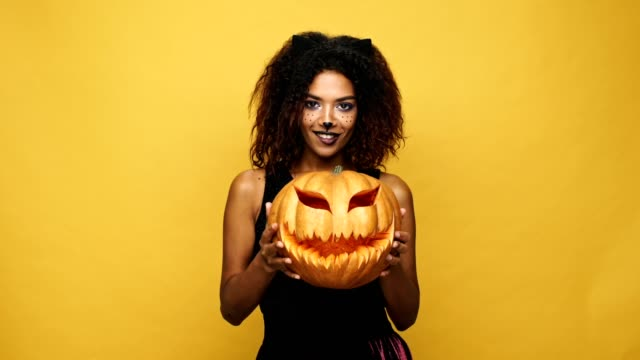Funny african lady in halloween costume showing and playing with pumpkin isolated over yellow background video