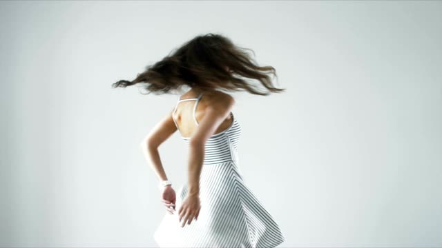 Funny attractive young female spinning in striped dress against light background video