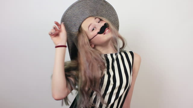 funny beautiful girl with hat and fake moustache having fun. - april fools day stock videos and b-roll footage