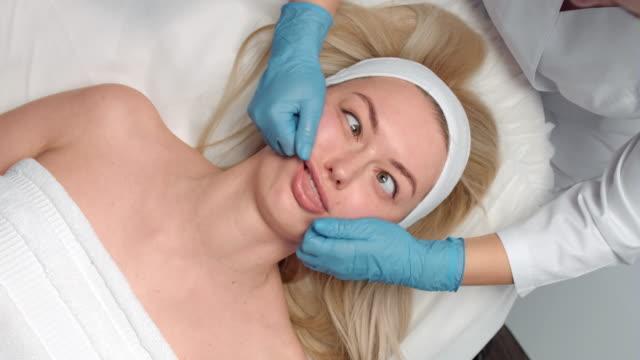 vídeos y material grabado en eventos de stock de chica rubia divertida tiene una sesión de masaje de belleza - medicina holística