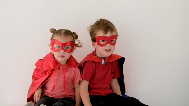 vídeos de stock e filmes b-roll de funny boy and girl in superheroes costumes clap hands - baby super hero