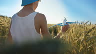 istock funny boy in a hat playing with airplane in wheat field, boy dreams of being a pilot 1284724182
