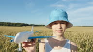 istock funny boy in a hat playing with airplane in wheat field, boy dreams of being a pilot 1284756259