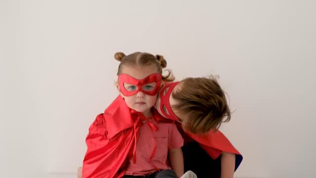 vídeos de stock e filmes b-roll de funny boy in superhero costume hugs and kisses little sister - baby super hero