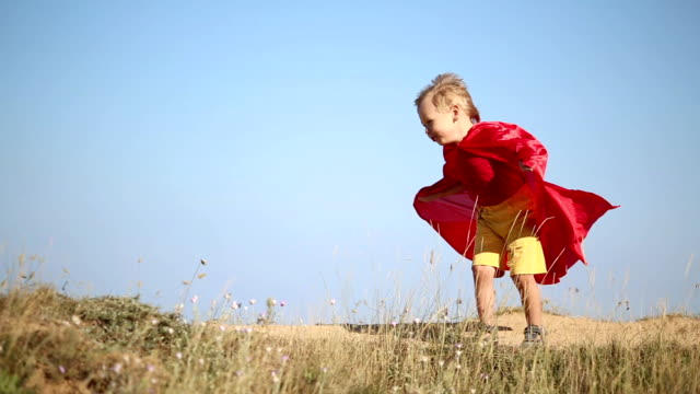 funny boy in superhero costume funny boy in superhero costume plays on the coast cape garment stock videos & royalty-free footage