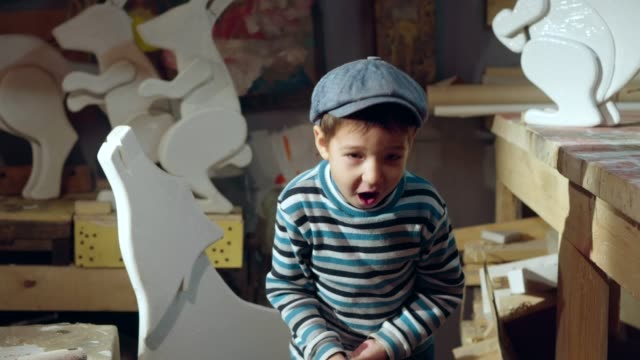 Funny boy is waving with paintbrush in home workshop video