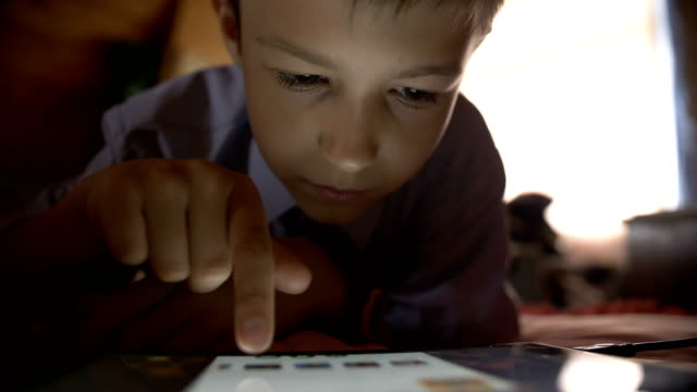 funny boy lays in a bed and touches on a tablet pc at home - solo un bambino maschio video stock e b–roll