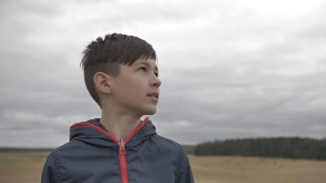 funny boy looks at the sky in autumn outdoors, rainy day, close up video