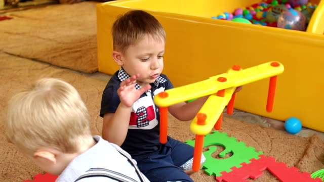 Funny boy plays with toys in kindergarten, slow mo video
