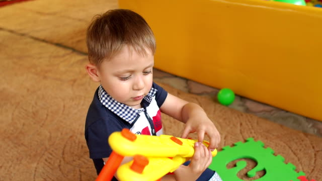 Funny boy plays with toys in kindergarten, slowmo. video