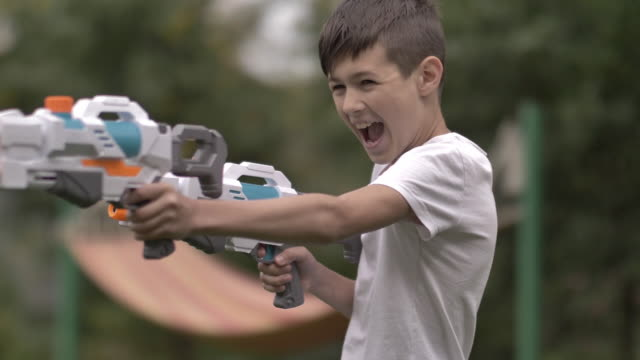 funny boy shoots with two water pistols outdoors in the village, have fun