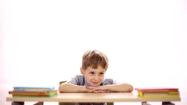 zabawny chłopiec siedzący przy biurku szkoły - negacja filmów i materiałów b-roll
