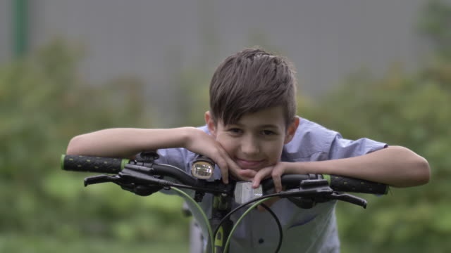 funny boy with a bicycle looking at the camera and smiling outdoors video