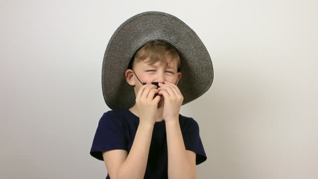 funny boy with hat and fake moustache on grey background. - april fools day stock videos and b-roll footage