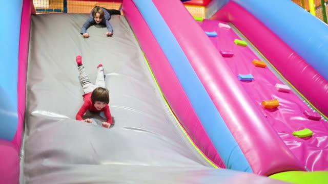 vídeos de stock, filmes e b-roll de meninos engraçados que jogam na corrediça inflada - inflável
