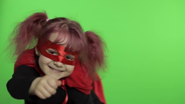 vídeos de stock e filmes b-roll de funny child girl in costume and mask plays super hero. national superhero day - super baby