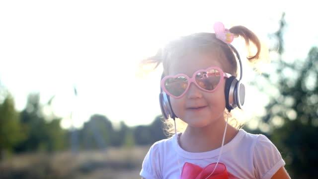 roliga barn i hörlurar lyssnar på musik, sjunger och dansar. härlig flicka i solglasögon vid solnedgången på en sommardag. livsstil - solglasögon bildbanksvideor och videomaterial från bakom kulisserna