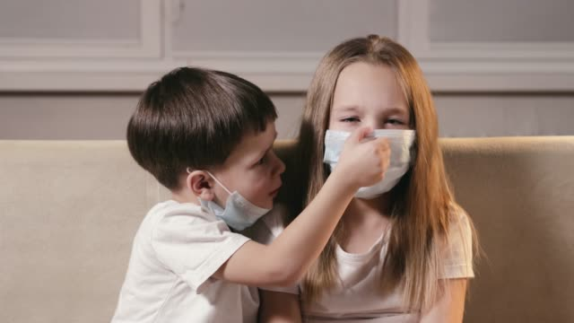 vidéos et rushes de des enfants drôles, un garçon et une fille ont mis des masques respiratoires sur leurs bouches et nez. protection contre le sras - enfant masque