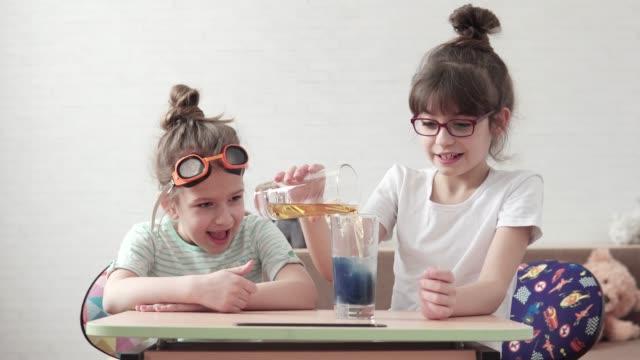 lustige kinder führen ein chemisches experiment und reagenzien zu mischen. kinder sind überrascht und glücklich, gerade die chemische reaktion - wissenschaftlerin stock-videos und b-roll-filmmaterial