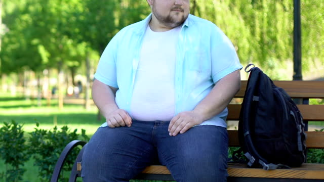 Funny chubby male sitting on bench in park and curiously looking at passersby Funny chubby male sitting on bench in park and curiously looking at passersby park bench stock videos & royalty-free footage