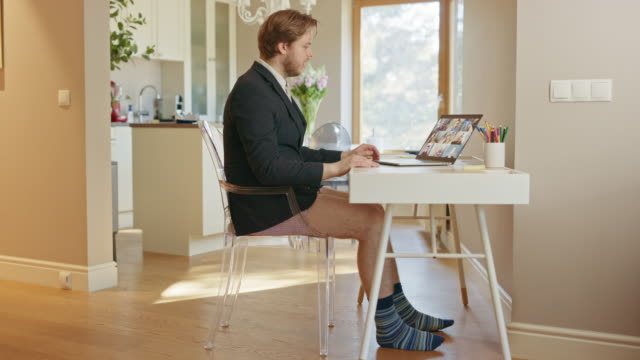 funny clip: businessman wearing jacket and no pants uses laptop and conference video call software app for board of directors online meeting. remote work, work at home, home office concept. side view - humor filmów i materiałów b-roll