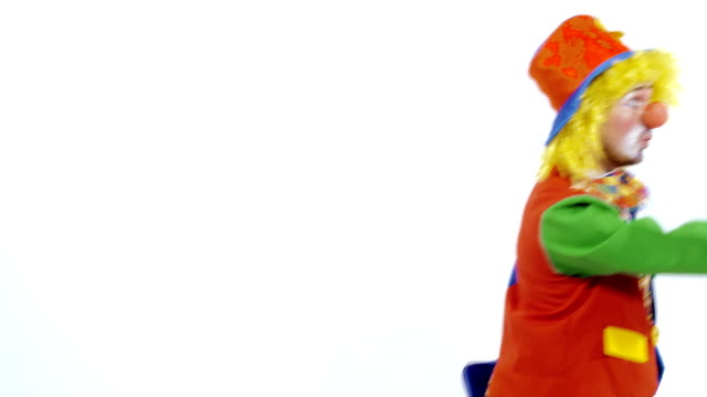 Funny clown walking backward showing colorful box and smiling in surprise video