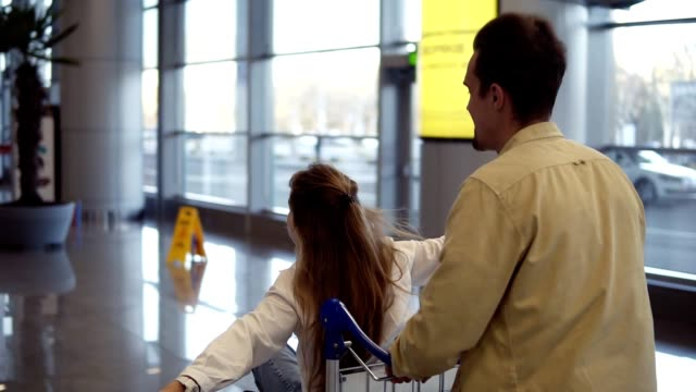 Funny couple in airport. Attractive young woman and handsome man with suitcases are ready for traveling. Having fun on luggage trolley while waiting for departure. Woman immitating flying, smilling, man running and pushing trolley. Rare view video