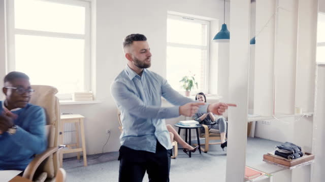 Funny crazy dancing businessman celebrating victory with excited multi-ethnic colleagues in modern light office 4K Funny crazy dancing young businessman celebrating victory with happy excited multi-ethnic colleagues in modern light office 4K. Millennial company boss doing a wild dance walk after achievement. excitement stock videos & royalty-free footage