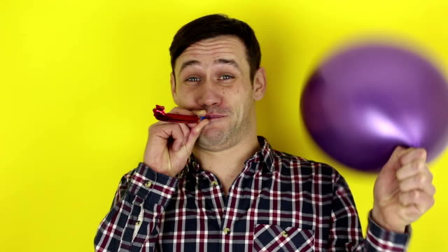 A funny, cute guy actively plays with a purple balloon and blows in a party horn.