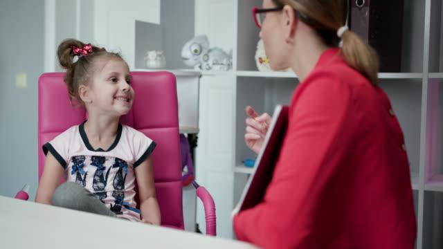 vidéos et rushes de drôle mignon enfant fille préscolaire apprendre la prononciation avec le concept d'orthophoniste, petit enfant préscolaire ayant problème de voix parlant la pratique sonne l'articulation pendant la leçon de langue avec l'enseignant - professeur(e)