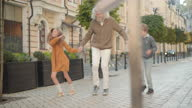 istock Funny dance of cheerful grandfather and grandchildren on sunny city street. Wide shot portrait of joyful senior man, little boy and girl dancing outdoors and leaving. Fun and leisure concept. 1282788379