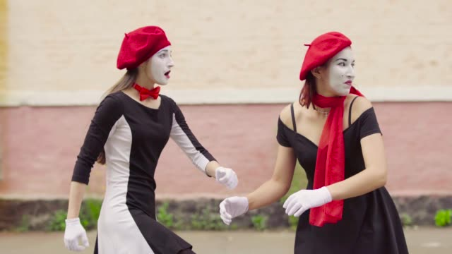 Funny dressed mimes make perfomance near building Company of three mimes, man and women in black dress do perfomance near building. Actors turn their head and body in funny way. Performance of street artists. Portrait of comics playing with facial expressions and gestures. greasepaint stock videos & royalty-free footage