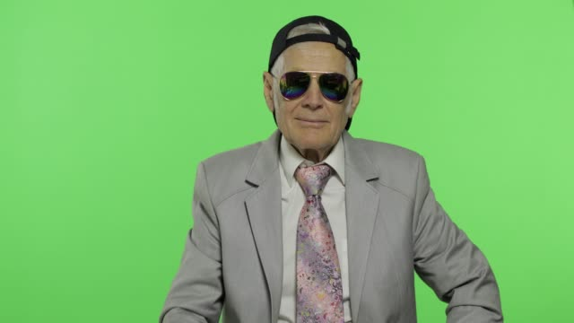 vídeos de stock e filmes b-roll de funny elderly businessman in sunglasses and cap smiles. old man winks - homem chapéu