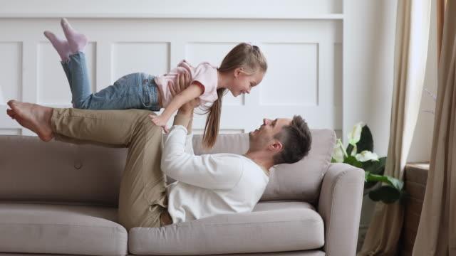 vídeos de stock, filmes e b-roll de filha bonito excitada engraçada que joga o plano com pai novo - pai e filha