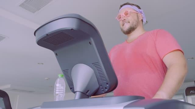 lustige dicke männchen in rosa brille und in einem rosa t-shirt ist auf einem laufband in der turnhalle darstellung ein mädchen engagiert. 4k - hantel stock-videos und b-roll-filmmaterial