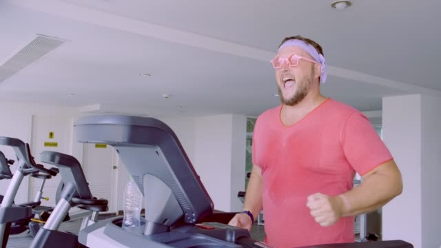 Funny fat male in pink glasses and in a pink t-shirt is engaged on a treadmill in the gym depicting a girl. 4k Funny fat male in pink glasses and in a pink t-shirt is engaged on a treadmill in the gym depicting a girl. 4k. macho stock videos & royalty-free footage
